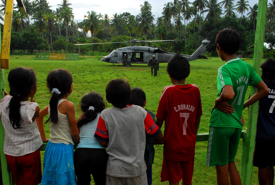 "Local Children Watch a Member from Helicopter Sea  Combat Squadron 23 ""Wild Cards"" Carry Float Coats for Passengers"