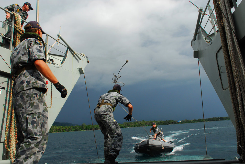 An Australian Royal Navy Sailor Throws a Line to Sailors