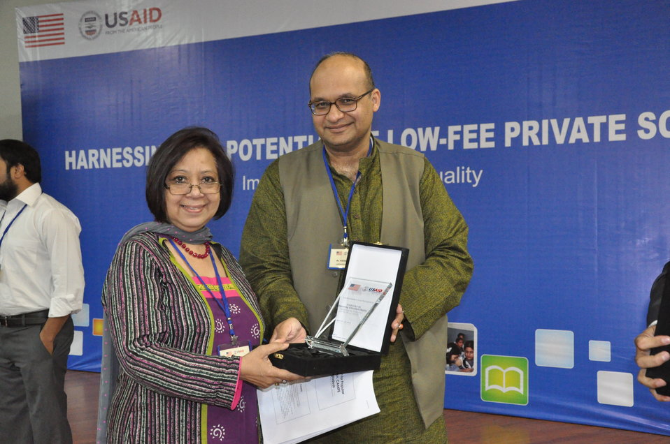 Dr. Faisal Bari, from LUMS, presenting a shield to Tasneem Athar from Bangladesh