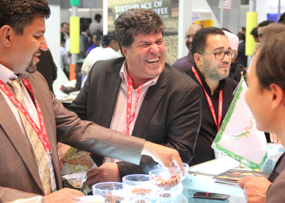 Visitors share a laugh with traders at the Afghanistan Pavilion over samples of the country's dried fruit and nuts. Afghan traders signed deals worth more than $2 million dollars during the first two days of the exhibition.