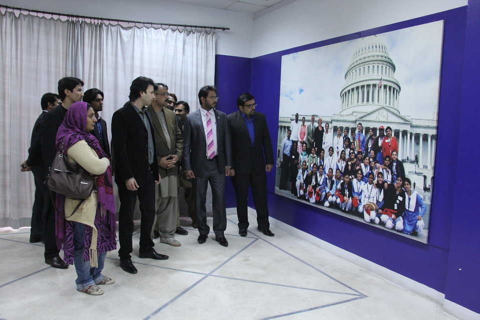 Attendees observe a photo from one of US-Pakistan Student Exchange programs.