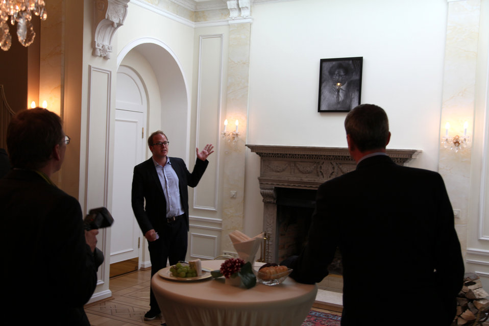 The Curator of an Art Exhibit Explains a Piece
