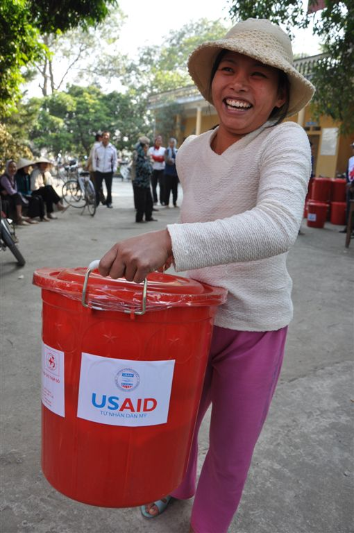 Thian Thi Ngoi from Lien Chau District carries home flood assistance supplies funded by USAID.