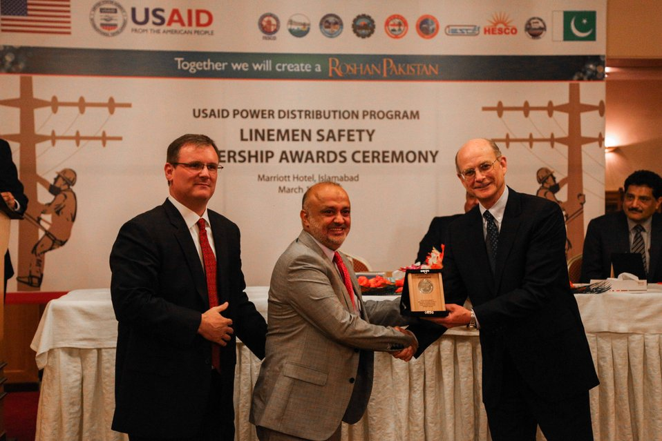 Saghir Ahmed receives an award from Michael Curtis