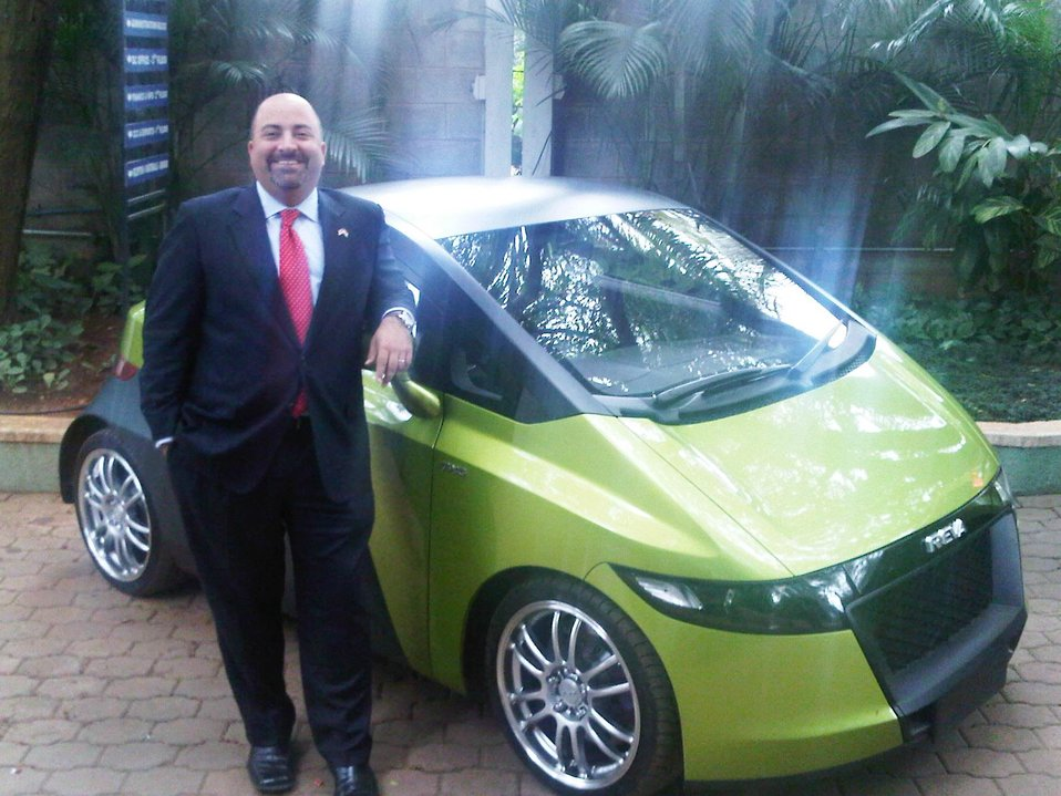 Acting Deputy Assistant Secretary Keshap Stands Beside a Mahindra Reva Electric Car