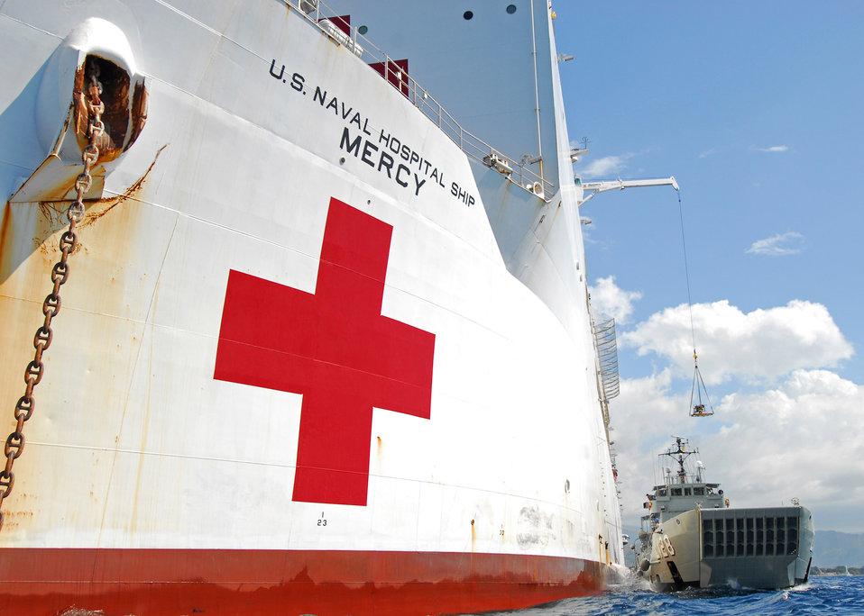 The Military Sealift Command Hospital Ship USNS Mercy (T-AH 19) Loads Cargo Aboard the Royal Australian Navy Heavy Landing Craft