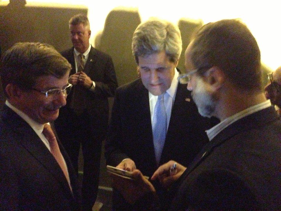 Secretary Kerry and Turkish Foreign Minister Davutoglu Look at a Photo