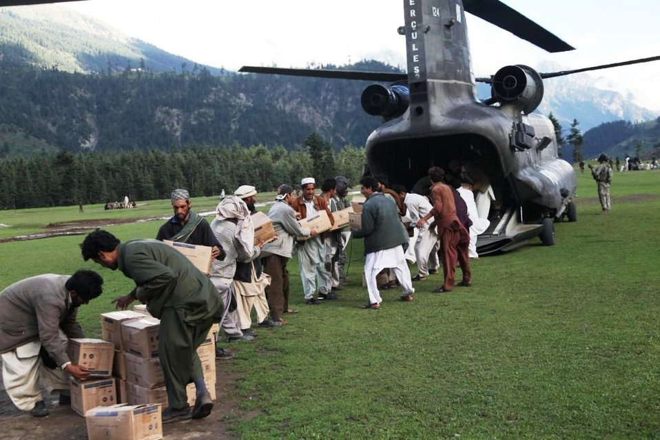 Men from Kalam Form a Chain To Unload a Helicopter