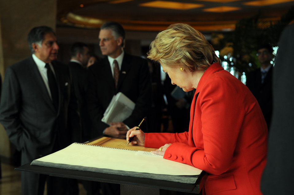 Secretary Clinton Signs Memorial Book at Taj Mahal Palace Hotel