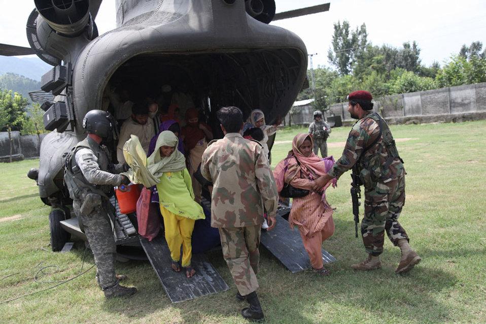 Members of the Pakistan Military Help Civilians Unload