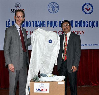 USAID Mission Director Joakim Parker, left, and Director General of Vietnam's Department of Animal Health, Dr. Pham Van Dong at the Protective Gear Handover Ceremony