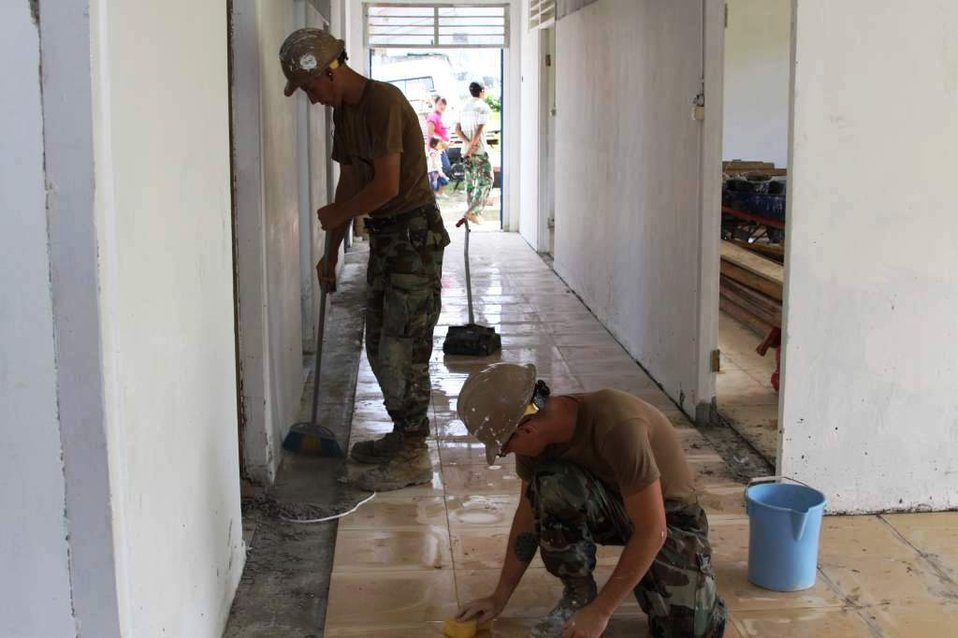Constructionman Steelworker Kenneth Ward and Constructionman Builder Matthew Ernst Prepare the Floor for New Tile at the Daruba Hospital Engineering Site