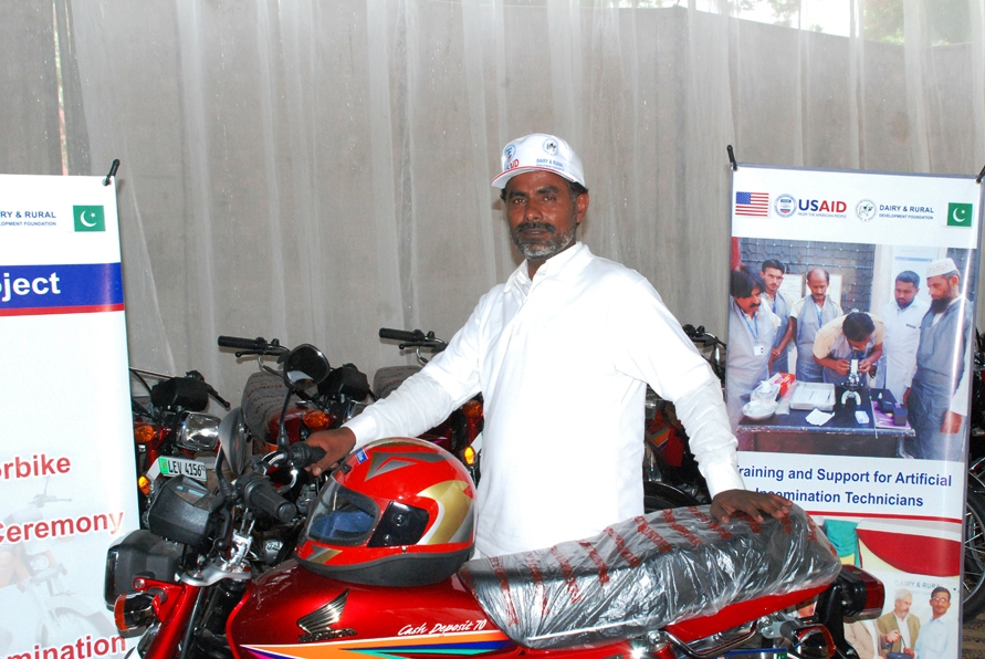 A successfull AI technician with his new motorcycle awarded by USAID Dairy Project