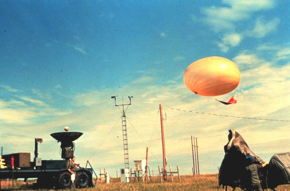 Large rawinsonde balloon is released in foreground It will measure atmospheric conditions during ascent.  In the background are surface weather instruments. These measure  temperature, relative humidity, pressure and precipitation. A mobile radar unit is