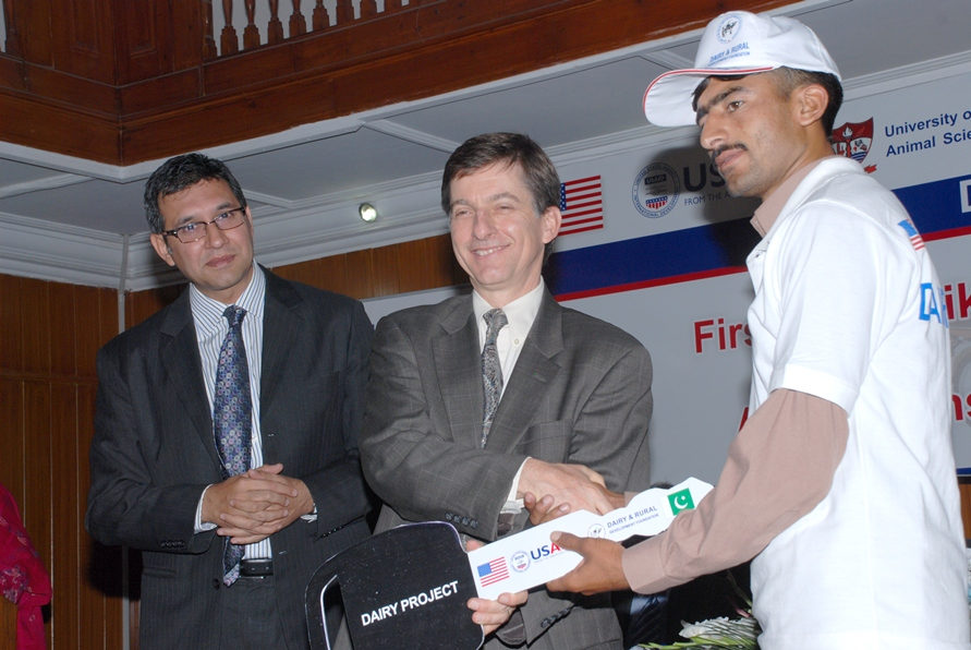 USAID Mission Director Dr. Andrew Sisson presenting motorcycle keys to a successfull AI technician