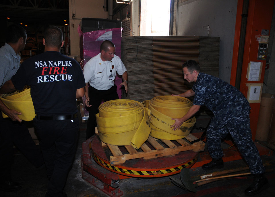 Logistic Specialist 2nd Class (SW) Vitali Toptchenko NSA Naples Lead Fire Inspector Hanz Christian, and Italian National Firefighters Maurazio Patrone and Alessio Storto Load a Pallet of Firefighting Equipment