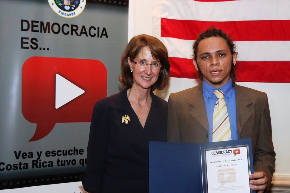 Ambassador Andrew Gives a Certificate to a Democracy Video Challenge Participant