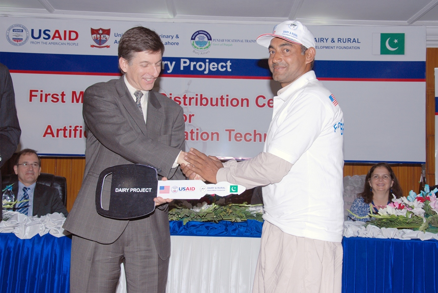 USAID Mission Director Dr. Andrew Sisson presenting motorcycle keys to a successfull AI technician 2