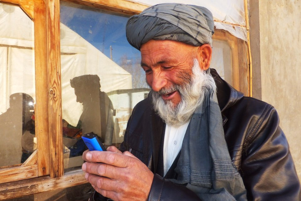 A Chaghcharan resident reading an SMS, highlighting government achievements, which was sent by the Ghor Deputy Provincial Governor on December 2