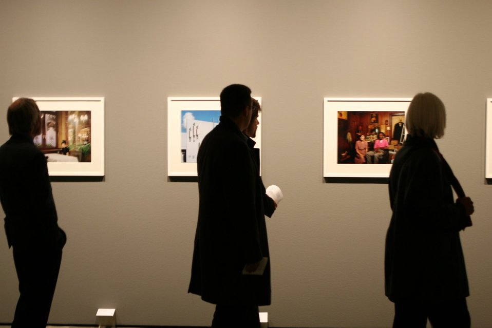 Viewers examine photography at the C/O Berlin Museum