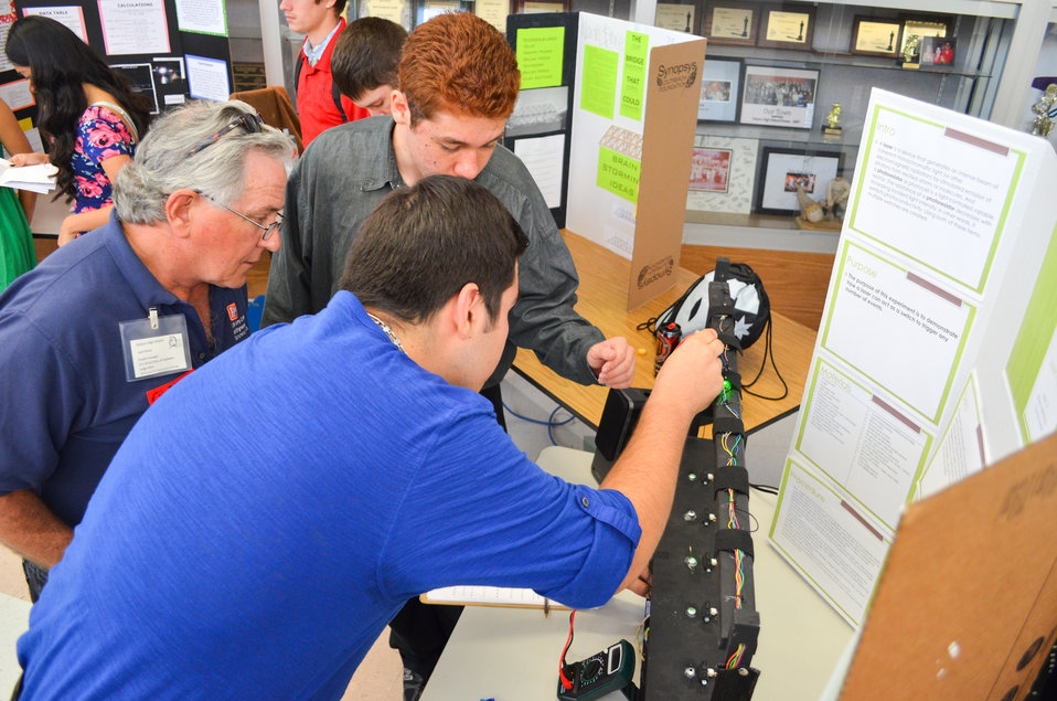 Jack Davies listens to students' voice synthesizer project