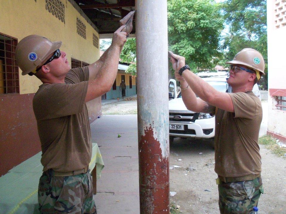 Utilitiesman 3rd Class (SCW) Hursh and Equipment Operator 3rd Class (SCW) Hicks Scrape Old Paint Off the Pillars