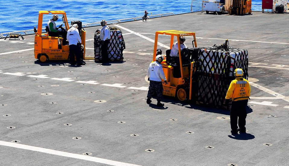 Sailors Clear Pallets of Cargo From Flight Deck