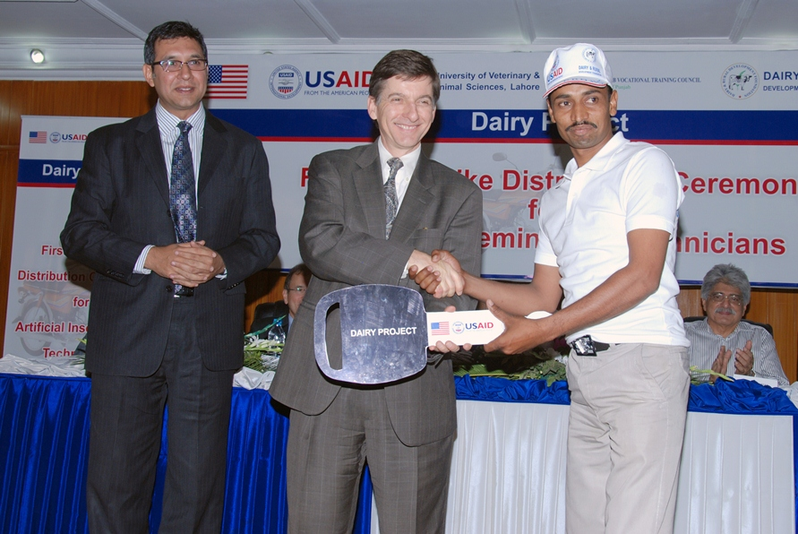 USAID Mission Director Dr. Andrew Sisson presenting motorcycle keys to a successfull AI technician 4