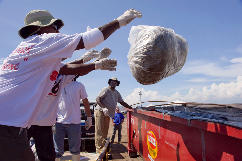 August 7, Work crews toss bagged waste into bins