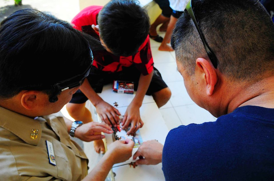 Command Master Chief, Master Chief Hospital Corpsman (SW/FMF) Noel Manlapaz and Master Chief Culinary Specialist (SW/AW) Jack Fong Piece Together a Puzzle With an Indonesian Boy