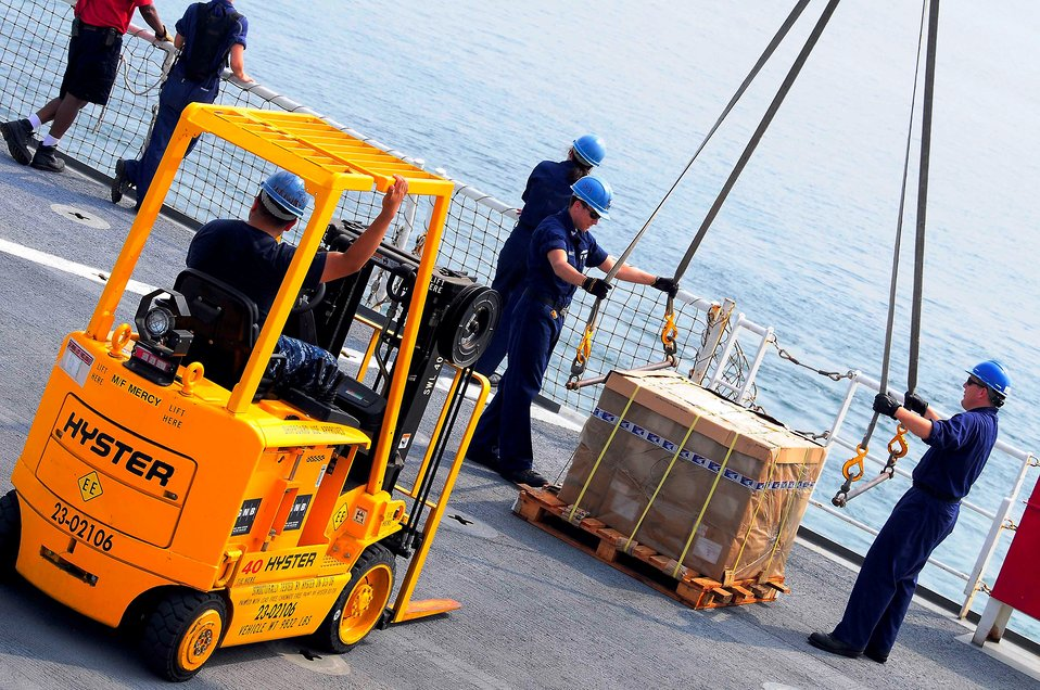 Sailors Remove Crane-Securing Straps From a Pallet of Medical Supplies