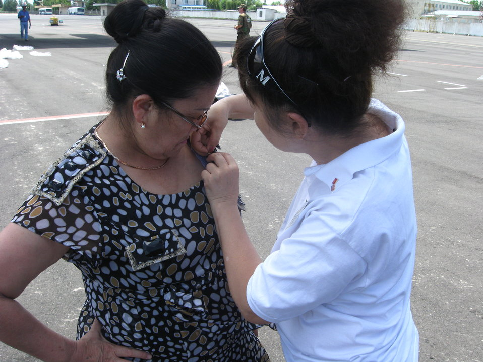 Bibira Akmoldoeva Helps Valentina Akimova of the Kyrgyz Republic Ministry of Health Put on a Flag Pin