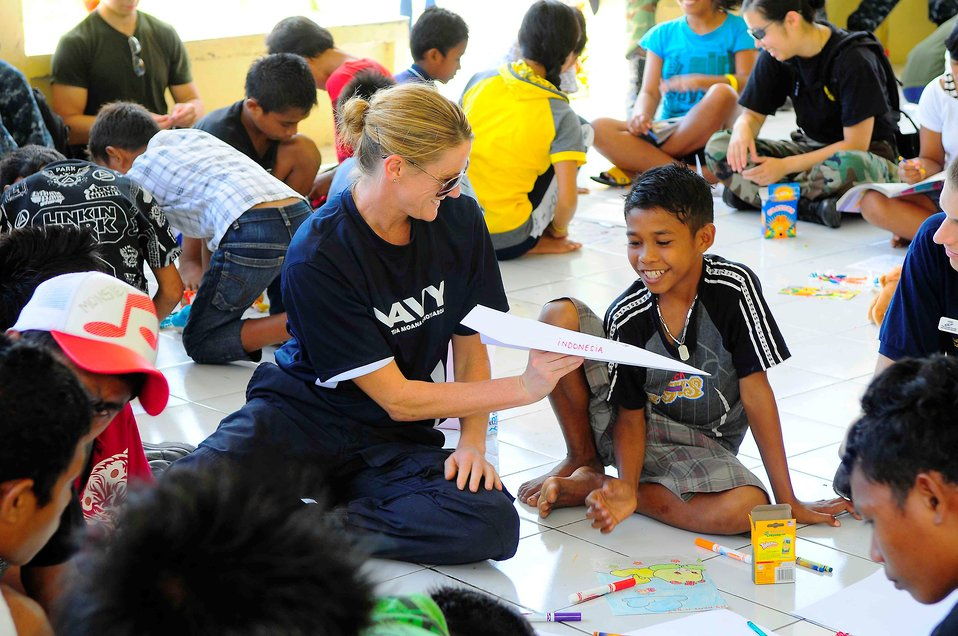 New Zealand Defence Force Lt. Cmdr. Kerry Climo Gives an Indonesian Boy a Paper Airplane