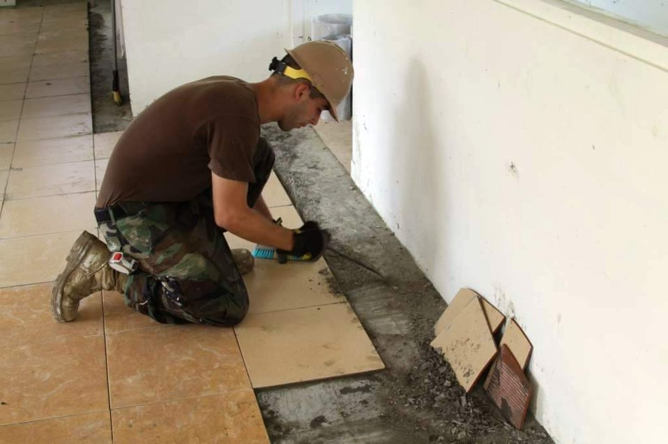 Cosntructionman Builder Jose Rivera Prepares the Ground To Lay Tile in the In-Patient Ward