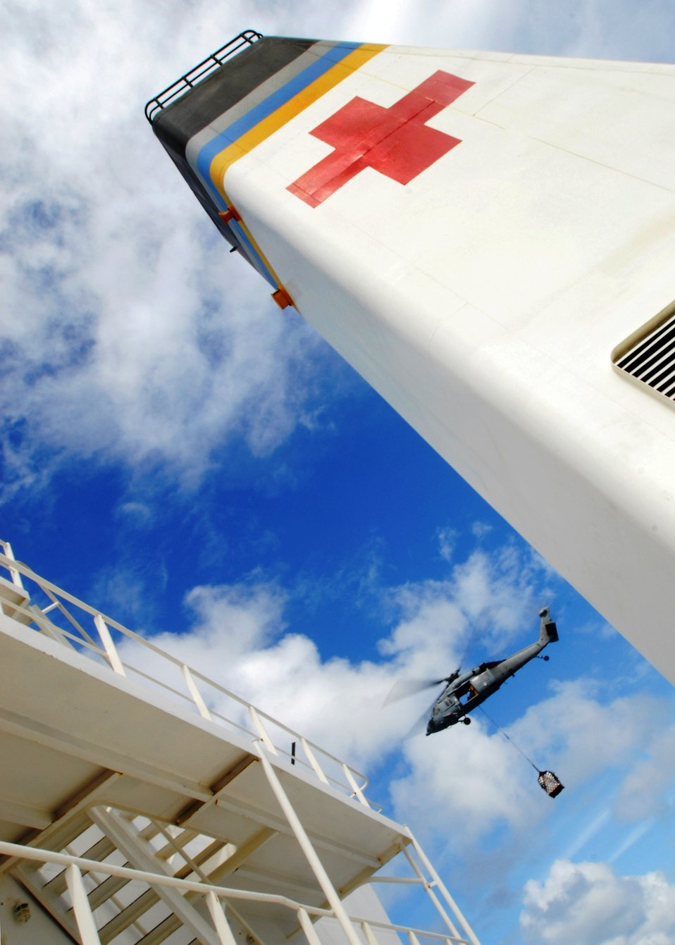 An MH-60S Knighthawk Helicopter Transports a Pallet of Goods to USNS Mercy