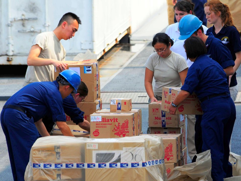 Sailors and NGO Volunteers Strip a Pallet of Medical Supplies