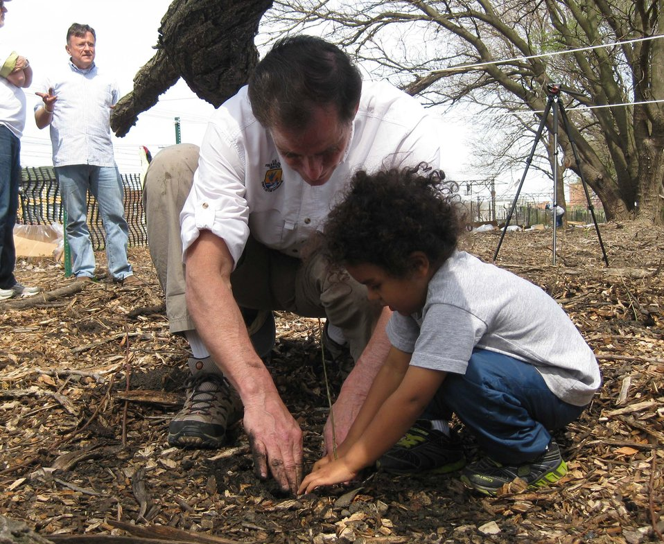 FWS Director Dan Ashe planting with young attendee