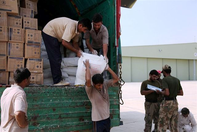 Pakistani Workers Unload Sacks of Flour from a Truck into a U.S. Army Helicopter