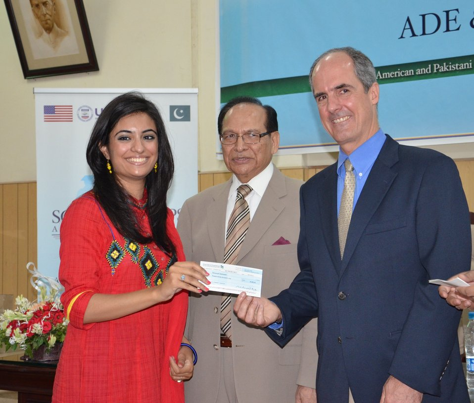 Mr. Ted Gehr, Regional Director USAID, awarding a scholarship to a student from Fatima Jinnah Women University