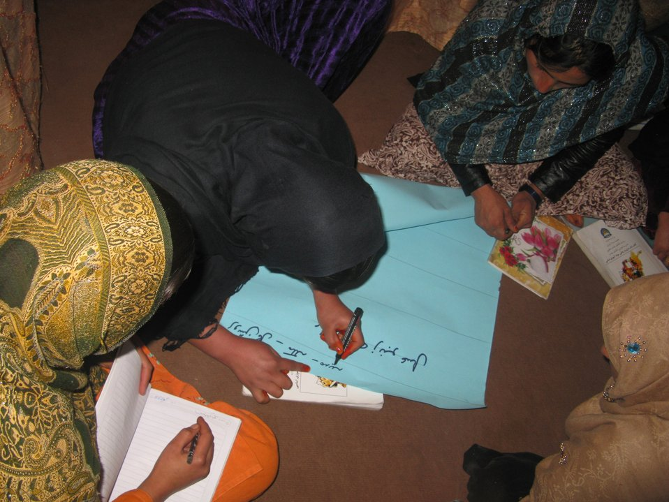 Female students work on a group assignment together in their home-based literacy class. Three months ago, these women were illiterate, while today they are comfortable reading and writing.