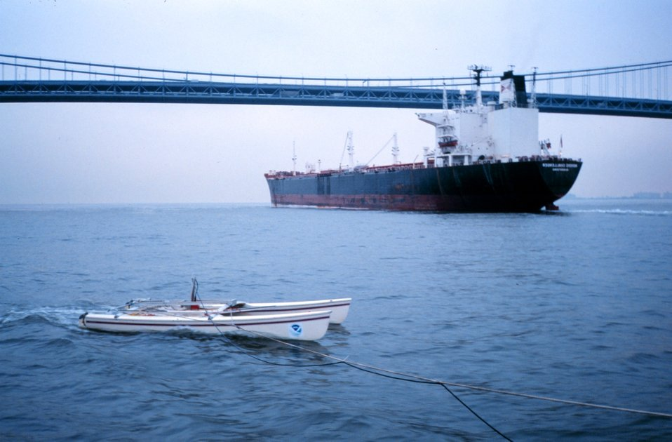An outbound ship passes under Verrazano Narrows Bridge as a NOAA modified catamaran takes mobile current profiles with an acoustic data collection platform (ADCP).