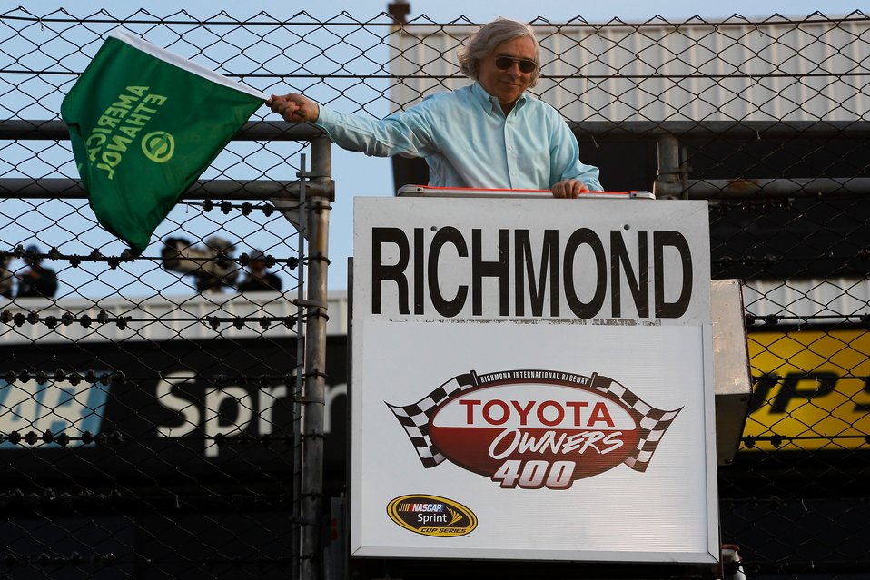 Secretary Ernest Moniz waves the green flag, signaling the start of the NASCAR Sprint Cup Series Toyota Owners 400 at Richmond International