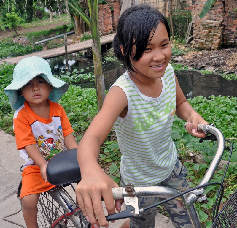 Children make their way by bicycle in Hung Yen village, Vietnam, where USAID works to fight avian influenza