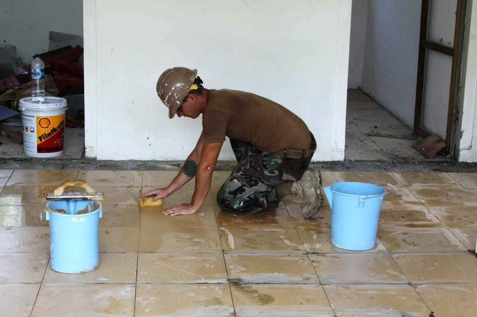 Constructionman Builder Matthew Ernst Cleans Freshly Laid Tile in the In-Patient Ward