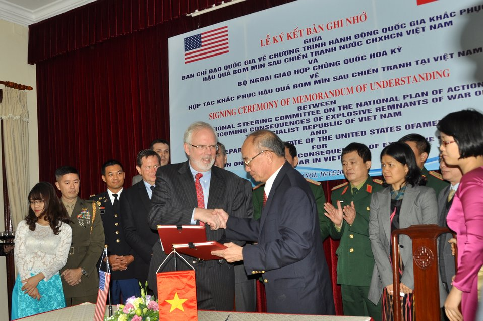 U.S. Embassador to Vietnam David Shear (left) and Mr. Bui Hong Linh, Vietnam's Vice-Minister of the Ministry of Labor, Invalids and Social Affairs (MOLISA) and Committee 504 Vice-Chairman, exchange the signed MoU.
