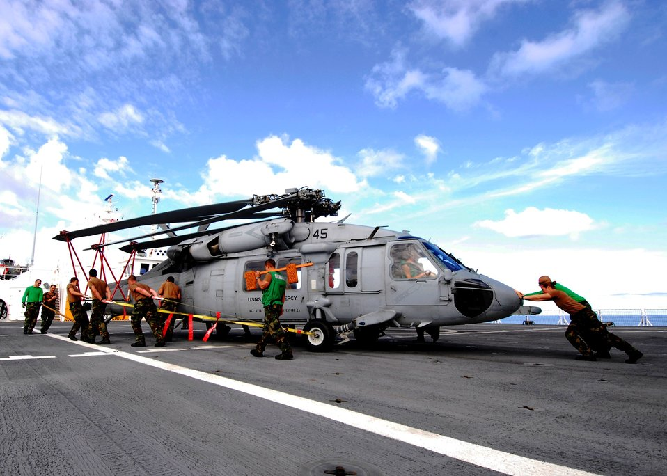 "Crew Members from Helicopter Sea Combat Squadron 23 ""Wild Cards"" Pull an MH-60S Knighthawk Helicopter Across the Flight Deck"