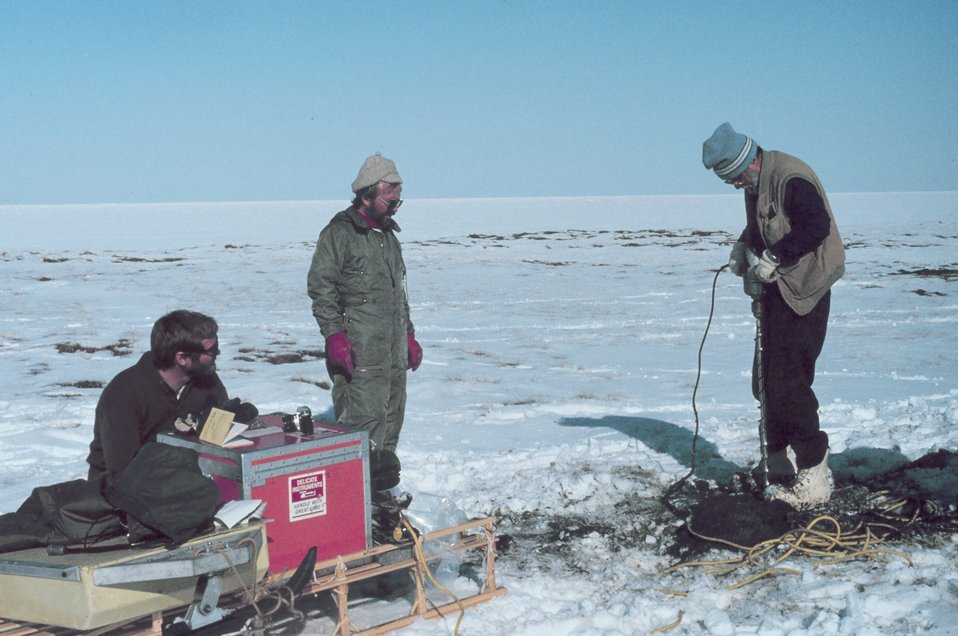 Scientists transported by helicopter drilling into permafrost as spring melting begins on Alaska North Slope.  Oceanic ice extends to the horizon.