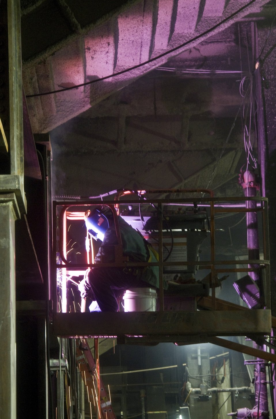 a welder at work on what will be the passenger concourse of the new LIRR station.