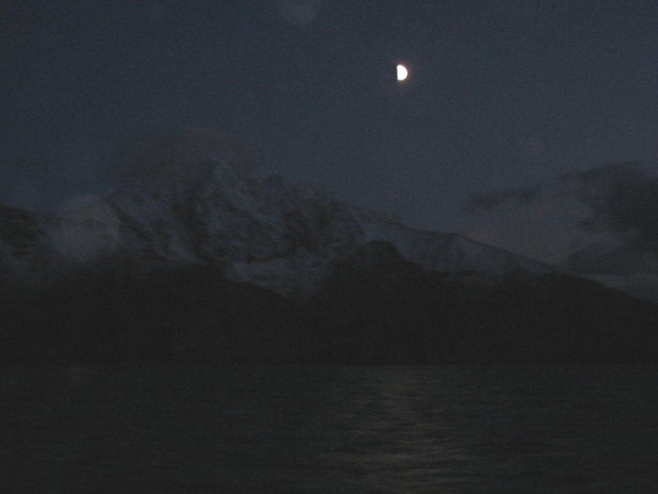 Night-time cruising in the Aleutian Islands. Moon  beams reflecting off the water as mountains are barely perceptible in the distance.