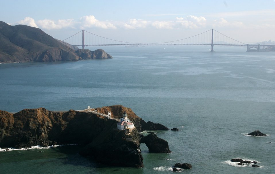 A magnificent view of the Point Bonita Lighthouse with the Golden Gate Bridge in  the background.